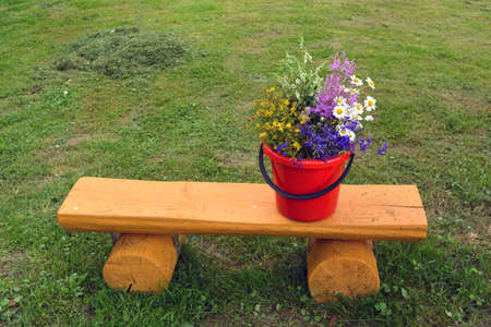 Various summertime wild flowers bouquet on yellow wooden bench in garden. Stock Photo