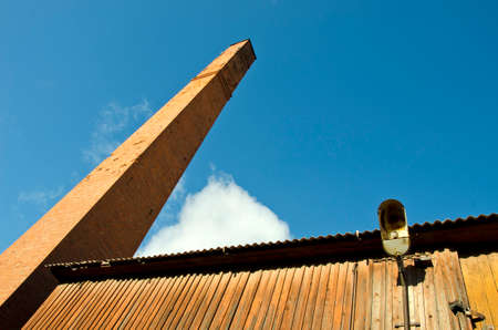 Old industriual building  with big red bricks chimney fragment