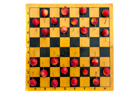 old wooden chessboard with red crab apples, harvest concept Stock Photo