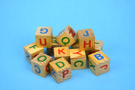 Alphabetical wooden retro cubes stack on blue background