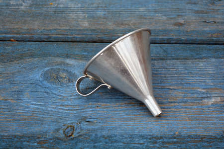 Vintage metal funnel with handle on old wooden blue garden table background