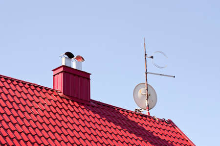 New private house red roof with chimney and TV disk Stock Photo