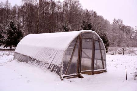Primitive plastic handmade greenhouse in winter farm garden Stock Photo