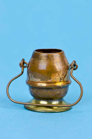 Decorative brass copper pot with handle on azure blue bacground Stock Photo