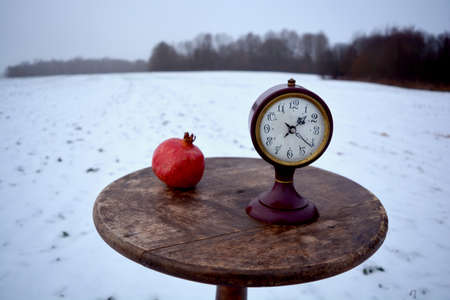 Winter still life with pomegranate and ancient clock on circle wooden retro table on snowy field Stock Photo