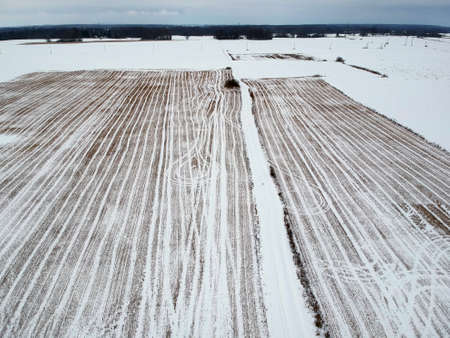 Winter time fallow  stubble agriculture field with snow, aerial view Stock Photo