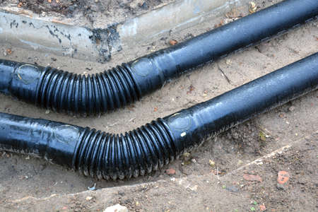 Two New black heating water tube pipe in trench