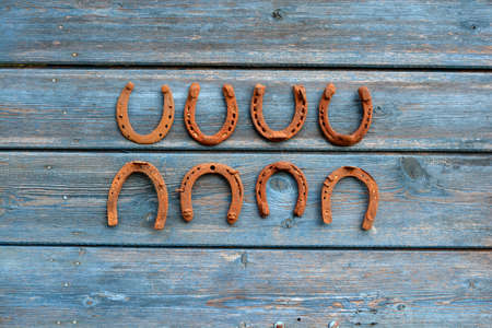 antica collezione di simboli a ferro di cavallo arrugginito sulla vecchia parete di legno