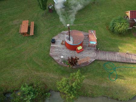 outdoor wooden barrel bath in summer garden, aerial Standard-Bild