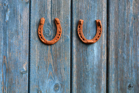 Two rusty luck symbol horseshoe on old wooden farm wall Archivio Fotografico
