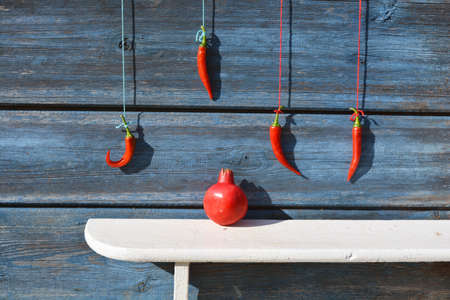 Red chili peppers hanging on wooden wall and pomegranate on white shelf