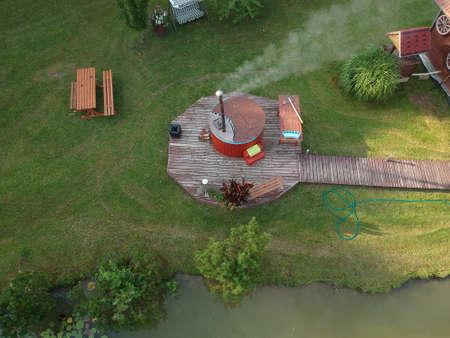 outdoor wooden barrel bath in summer homestead, aerial