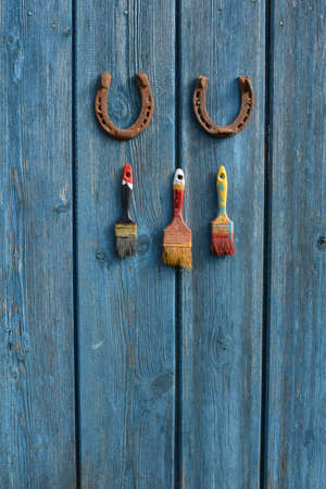 Hang on blue old wall two rusty horseshoe and three brushes