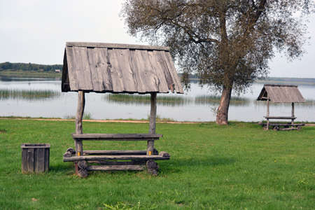 Old wooden handmade bench with roof near lake for tourists