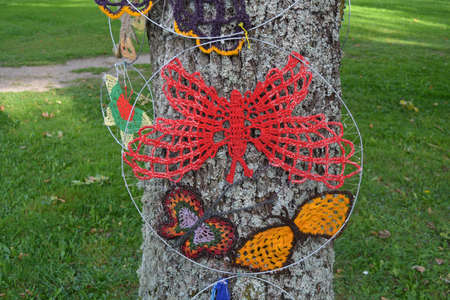 Colorful knitted butterflies on tree in summer park
