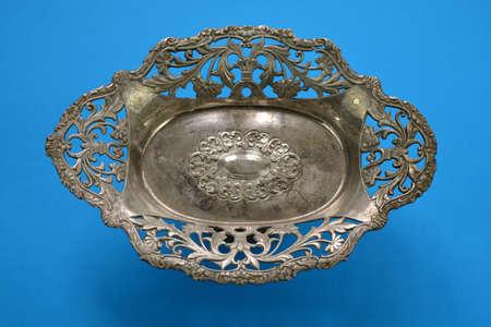 Vintage ornamental metal vase on blue background