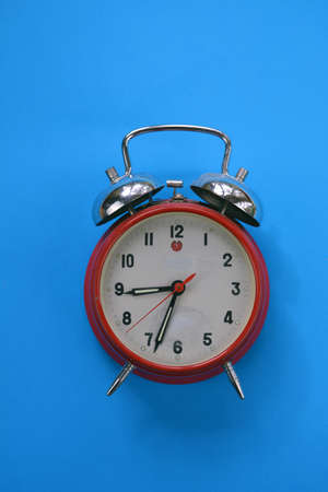 red old retro style alarm clock on blue background Stockfoto