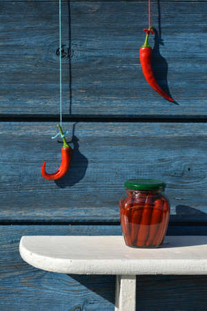 Canned glass jar on shelf and red hot chili pepper hand on wall