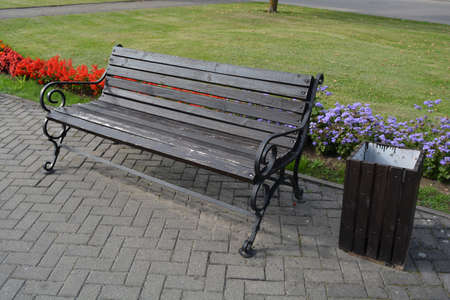 Modern wooden bench with metal frame in city street and flowerbeds