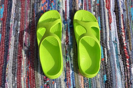 Pair plastic green sandals on handmade carpet background