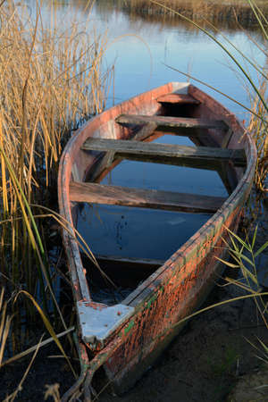 Lonely old wooden fishing boat on autumn lake coast with rain water