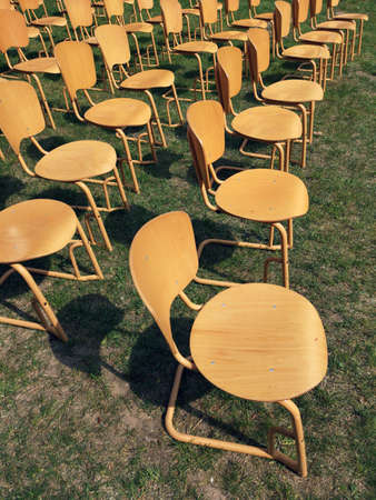 Group of yellow chairs, standing outside in the park in front of the stage