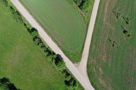 Aerial view of gravel road on farm fields in spring
