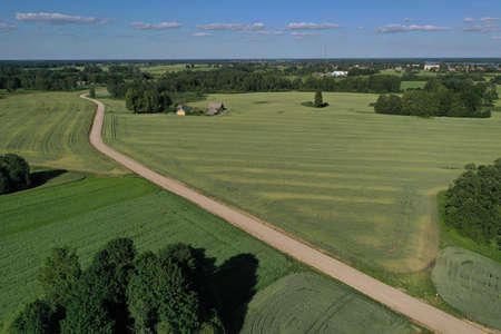 Aerial view of gravel road on farmland fields in summer