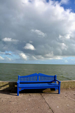Empty wooden blue bench with sea view on concrete pier