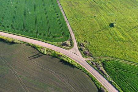 Spring time farmland fields and gravel roads, aerial view