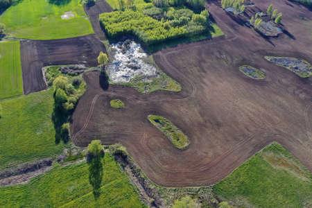 freshly Plowed wet early spring field in nature park, aerial view