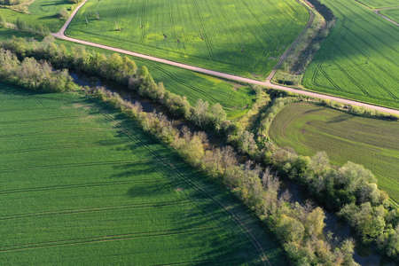 Beautiful spring time farmland landscape with river and gravel road, aerial view