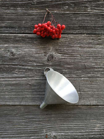 bunch rowan berries and new metal funnel hanging on old wooden wall Stok Fotoğraf