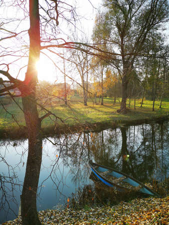 Autumn morning sunrise and beautiful river with wooden fishing boat