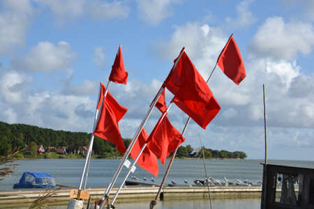 Red fishing flags group near sea and pier