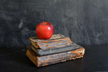 Still life with Old damaged holy bibles and red apple on dark background Stok Fotoğraf