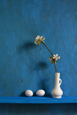 Still life with white vase, apple tree blossoming branches and two eggs