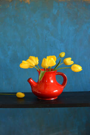 bouquet of yellow tulips in red vase on black shelf