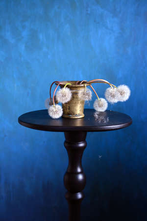 Still life with antique brass Mortar and dried fluffy dandelions heads