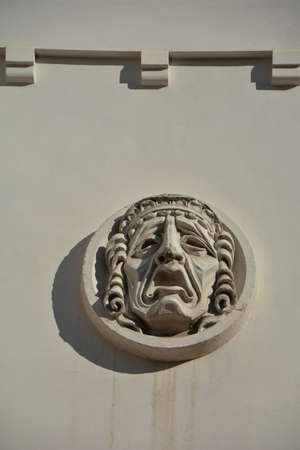 Plaster mask symbol on old wall of the theater