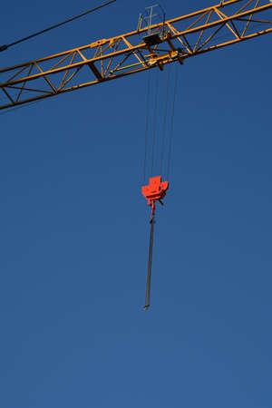Building crane boom with steel hook on sky background