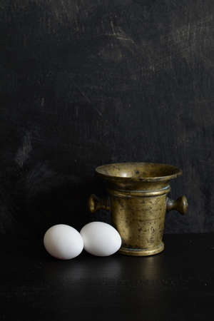 Still life with Antique brass Mortar and two white eggs on dark background