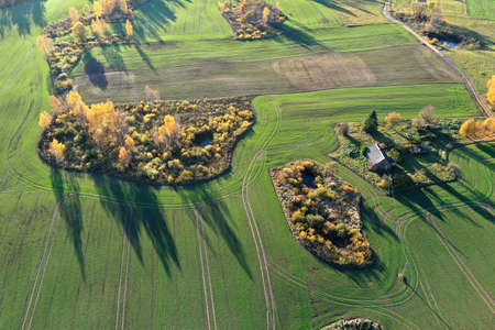 beautiful autumn landscape with fields, groves and old homestead in nature park, Lithuania, aerial view