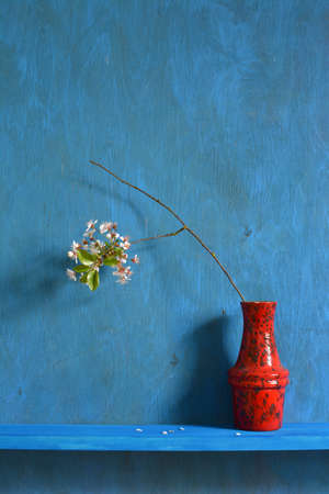 Still life with red vase and blossoming cherry branch on shelf