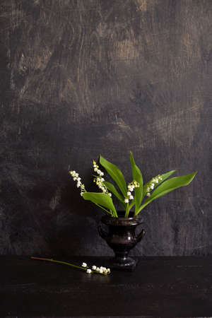 Bouquet flowers Lily of the valley Convallaria majalis in black vase on black background Stok Fotoğraf