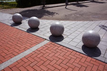 Four decorative granite balls spheres on sidewalk in street