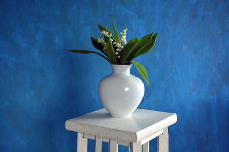 Bouquet flowers Lily of the valley Convallaria majalis in white vase on white table