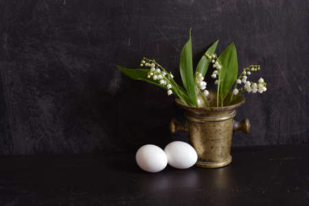 flowers Lily of the valley Convallaria majalis in old brass mortar and two eggs Stok Fotoğraf