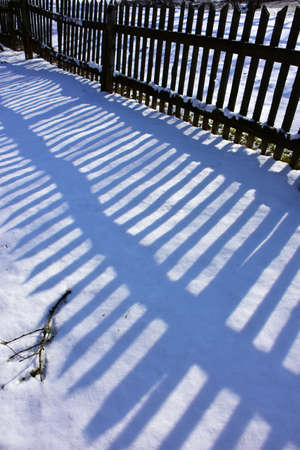 Wooden old fence shadow on winter snow