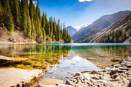 Majestic mountain lake with green trees in Kazakhstan